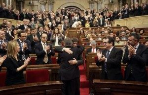 epa05095790 Catalonian acting President Artur Mas (front) embraces Gerona's Mayor Carles Puigdemont (C back) during the Puigdemont's vote of confindence in the regional Parliament in Barcelona, northeastern Spain, 10 January 2016. An alliance of pro-separatist parties in Catalonia on 09 January struck a last-minute deal to form a new regional government, after months of wrangling that threatened to undermine a fresh bid for independence from Spain. The Together for Yes (Junts pel Si) alliance, led by acting President Artur Mas, ceded to the demand of the leftist CUP party that Mas step down. In return, CUP entered into a coalition with Together for Yes. Carles Puigdemont, a former journalist and mayor of the Catalan town of Girona, will replace Mas as president, a position he held since 2010.  EPA/ALBERTO ESTEVEZ